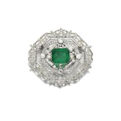 EMERALD AND DIAMOND BROOCH, 1910S Designed as an octagonal plaque, pierced and millegrain-set with astep-cut emerald, circular-, single-cut, rose and baguette diamonds.