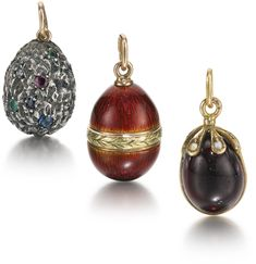 Three Fabergé egg pendants: the first of nugget-textured silver inset with circular-cut diamonds, emeralds, rubies and sapphires, Moscow, 1899-1908; the second in translucent red enamel over a hatched surface with gold leaf-tip band, St Petersburg, circa 1910, workmaster Feodor Afanassiev; the third a carved garnet with gold and seed pearl cap and ring, circa 1895.