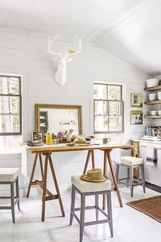 With the kitchen's narrow layout, there wasn't room for a breakfast table and a prep island, so the Brewers drew up a plan in the form of an antique drafting table. When it's not used as a work space, it's a particularly cozy gathering spot, thanks to custom-made cowhide-covered stools.
