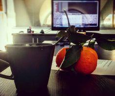 Meetings με προγραμματιστές. Πίσω η οθόνη δείχνει κώδικα που δεν καταλαβαίνω. Σε πρώτο πλάνο πράγματα που καταλαβαίνω: καφές και μανταρίνια που δίνουν άρωμα στο meeting room. Launching soon!!!! by marilou_tze