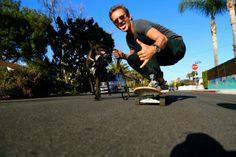Sebastian Roché walking his dog. while skateboarding.