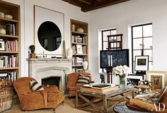 A large-scale work on paper by Richard Serra is given pride of place in the living area of a Manhattan apartment, where an LG flat-screen television is mounted on an artist's easel. A pair of Ralph Lauren Home club chairs and a vintage horn stool are grouped with a cocktail table by Lucca Antiques.