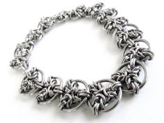 This one is special. I made it by adapting the ancient and amazing pattern called Byzantine. I first use that pattern to create the triple sided sections which I then connect with the larger rings to make this incredibly unique style of chain. I make all of my chains from scratch;