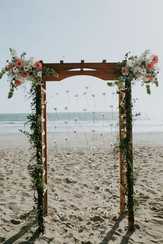 SWOON! What a beautiful wooden arch! The couple decorated with daisy chains, garlands and floral arrangments that match the bridal bouquet   Seafoam & Coral Ventura Beach Wedding // Wedgewood Ventura