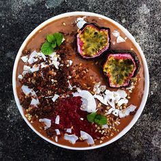 cacao smoothiebowl topped with passionfruit, homemade raspberry chia jam, date-almond crumble, coconut flakes, buckwheat groats & flaxseeds ~