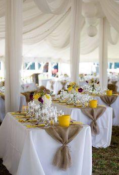 Decoración de boda rústica con arpillera y amarillo, que se destaca en las cubetas, cubierta con una carpa de bodas en blanco.