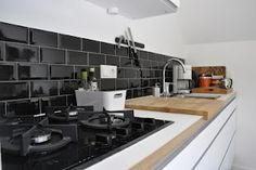 kitchen design by Urban Empire with black tiles and basics from Ikea faktum