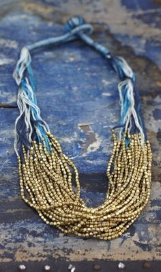 Very pretty necklace, added by a pinner, with blue and white thread and gold beads. Good DIY idea.