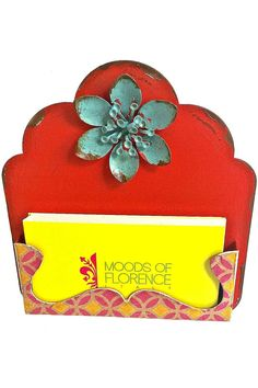 """Adorable metal business card holder in assorted color painted metal; has a rustic vintage look on surface and around the edges. Contrasting metal flower center on top with scroll floral painted holder bottom. and metal easel on back.  Measures 5""""H X 4 1/2""""W X 1/2""""D  Business Card Holder by Midwest CBK. Home & Gifts - Gifts - Odds & Ends Portland Oregon"""
