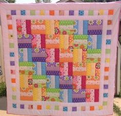 Bright geometric quilt made with fabric from Modas Good Morning line with light pink backing. Hand quilted. Made with 100% cotton fabrics. Created in non-smoking environment. Approximately 48 x 48. Great size for baby play time. Add customized quilt tag for $10.