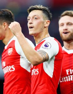 Mesut Ozil of Arsenal celebrates scoring his sides third goal with his team mates during the Premier League match between Arsenal and Chelsea at the Emirates Stadium on September 24, 2016 in London, England.
