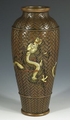 "A copper-patinated bronze vase marvelously carved as a bamboo basket, a writhing, gold dragon emerging from chiseled breaks in its side. This vase is so realistically modeled, the bamboo so natural and the dragon's scales so real that it is awe-inspiring to behold. Hamada Terunao elaborately engraved signature on base. Height, 8.25"". Meiji Period."