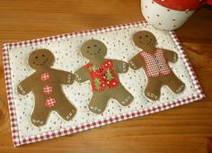 """These little fellows are from my Gingerbread Cup pattern - three of the gingerbread men on a 10"""" x 6"""" background.   I love that one little $1.99 pattern creates two very different mug rugs - great value for money."""