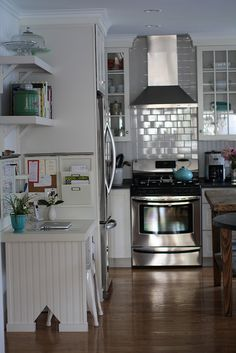 white tiles, white shelves, white cabinets, glass cabinets (turquoise teapot!)