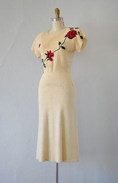 1940s cream knit dress with rose motif on the bodice. Vintage 40s sweater dress has a va-va-voom bombshell fit with short cap sleeves and slight tulip flare to the hem.