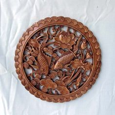 Chinese wood carvings are framed art with folk art craftsmanship and in design of drawing two finish is swimming in the pond beside lotus flower.