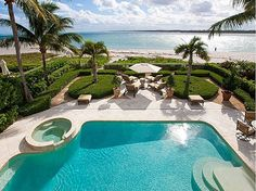 Turquoise ocean waters are steps away in this tropical backyard. #pool #summer #dreamhome
