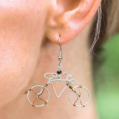 "Bike Earrings: Perfect for the stylish cyclist, these Fair Trade bike earrings are made of delicate wires molded into the shape of a two-wheeler. A black bead focal piece and copper accents make the earrings really stand out. Made of wire, plastic bead and steel. 1½""W x 1""H."