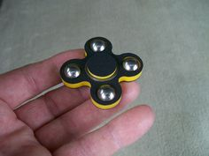 """New from JWraps - """"The Mini Quad Dual Color"""" Fidget Spinner EDC Toy in Black & Yellow Sandwich Hard Plastic Colors - $22.95 plus $3.00 shipping Crafted from High Density (HDPE) solid marine grade plastic and hand fitted bearings. Designed to last. NOT 3D printed - won't warp or break. Other wrap designs available. In stock, ready to ship! Purchase at our website: ohsnapproducts.com"""