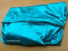 Hoes gemaakt van groene satijnen ochtendjas. De zomen zijn in laagjes op elkaar gestikt en voelen als ribbels. De plooien laten de stof golven en bieden ruimte aan het materiaal/kleding die in de hoes wordt gekoesterd.