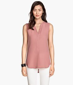 Check this out! Sleeveless V-neck blouse in woven fabric. Concealed buttons at front, raw edges at neckline and armholes, and rounded hem. Slightly longer at back. - Visit hm.com to see more.