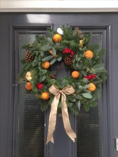 Traditional wreath with a gold bow - made up from whole dried oranges, pine cones, red berries, cinnamon bundles, sliced apples, on a populus and pine foliage base.