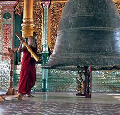 Young buddhist monk ring the bell in Myanmar; by John Glines