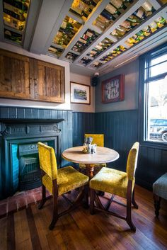 Interior decor inspiration, mustard velvet chairs, blue tiled fireplace, upcycled wine bottle ceiling ideas in traditional English pub restaurant In the midst of a vibrant area of Cambridge, The Peter