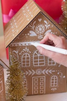 Inspirations et idées pour Noël : DIY Gingerbread house gift boxesDIY Gingerbread house gift boxes - I have to do this next Christmas.DIY gingerbread house gift box created with cardboard and paint markers.These gingerbread house gift boxes are ado Cardboard Gingerbread House, Christmas Gingerbread, Noel Christmas, Christmas Projects, Gingerbread Houses, Christmas Ideas, Christmas Houses, White Gingerbread House, Cardboard Box Houses