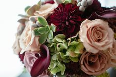 The bouquet was rich in colors and full of hydrangeas, burgundy dahlias, amnesia, black magic roses, and a few gray berries.