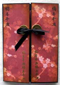 handmade gatefold card ... gorgeous print paper ... muted reds with sakura .... embossed Japanese script lines ... coins with ribbon tie up the card ... wonderful! ... Crafter's Companion