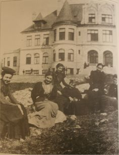 Young women students relax on the lawn in front of Denny Hall at the University of Washington which housed the student YWCA.  1898.