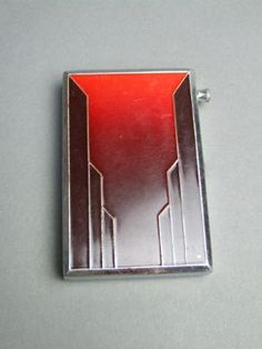French Cigarette Case and Lighter with red enamel cover and engine turned back panel. Inside there are cigarette holder clips and a striker lighter which unscrews from the lighter and there is a striker panel to one end. It measures 3.75 inches by 2.75 (9.5cm x 7).