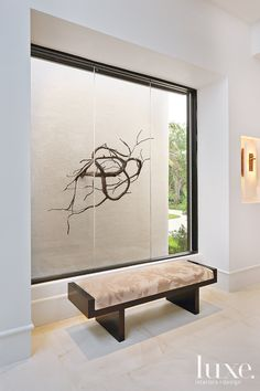 A bench from Carriage House takes  a seat before the picture window in  the entry foyer that spotlights a  cast-bronze branch sculpture from  J. Batchelor... Love! Interior Design: Robert M. Krych and Kris M. Kocher Architect: Shane Ames Photography: Michael Stavardis Florida Fall 2010 #Luxe