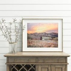 Can you imagine waking up in a home that perfectly reflects your style and sparks inspiration for your next adventure. This modern photography art print is a rustic farmhouse with a pastel colored sunset against the mountain backdrop. These soothing colors will create a focal point in your home decor. The scenic country farm with a field is a perfect picture for your farmhouse and country decor. Click to see options and other barn photography. #barnpictures #rusticfarm #mountainphoto #sunset