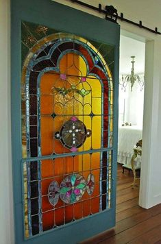 An antique stained glass door hung with barn door hardware becomes the centerpiece of this cottage bungalow. Stained Glass Door, Leaded Glass, Mosaic Glass, Mosaic Mirrors, Mosaic Wall, Beveled Glass, Glass Barn Doors, Sliding Glass Door, Sliding Doors