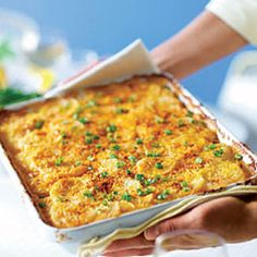 Scalloped Potatoes: Ingredients: -5 tablespoon(s) flour  -3 cup(s) milk  -1 bag(s) (8 oz) shredded American and Cheddar Jack cheese blend (such as Kraft Classic Melts)  -4 tablespoon(s) grated Parmesan cheese  -2 teaspoon(s) Dijon mustard  -1 teaspoon(s) salt  -3/4 teaspoon(s) paprika  -3 pound(s) (6 large) baking potatoes, peeled and sliced 1⁄8 in. thick (10 cups)  -1/4 cup(s) sliced scallions