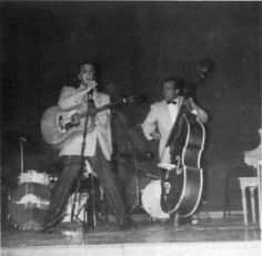 "Elvis and Bill during second show in the fieldhouse - May 27, 1956 Photo courtesy Brian Petersen's ""Atomic Powered Singer""  That primitive almost savage expression may be, in itself, a part of the hypnotic fascination. Then, too, the young southerner with straight, slicked-back hair and long sideburns, is dedicated to his audience. He sets his course and steers it straight, completely oblivious and uninhibited 