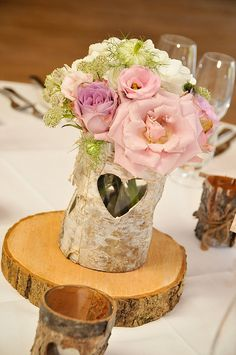 Bark vases and wooden tree slices / tree slabs can make amazing rustic centrepieces.  Bark vases and tree slices available from www.theweddingofmydreams.co.uk
