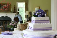 Wedding cake with purple ribbon and flowers