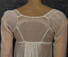 The constrained pattern of the lace is typical of the Neoclassical period. The superbly shaped back of the dress ends in a graceful train.