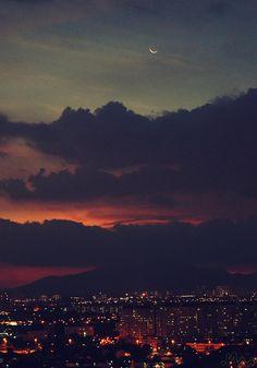 Cette image représente la ville lors du coucher du soleil par photographie. Vers le bas, on y retrouve la ville avec toutes ces lumières. Vers le haut, on y retrouve le dégradé d'orangé et rosé en arrière des nuages. On y retrouve aussi la lune tout en haut. Je ressens le calme parce que c'est le paysage du soir est apaisent et relaxant.