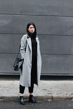 Elisa from the Fashion- and Lifestyleblog www.schwarzersamt.com shows a minimalstic autumn winter look with a woolen grey Long Coat from Primark, a black sweater from FUNKTIONSCHNITT, a big black bucket bag from PIECES via ABOUT YOU, black loose fit pants from H&M and VAGABOND chelsea boots . It's a perfect look for the colder autumn or winter days, winter stylings, coat trends, grey coats