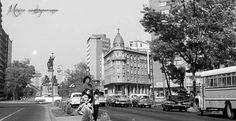 Familia espera a que pasen los autos para cruzar el Paseo de la Reforma, en las inmediaciones de la Glorieta de Colón, a inicios de los años sesenta. Del lado derecho se aprecia el Hotel Imperial, y al fondo, los anuncios de Coca - Cola y Pepsi en los edificios cercanos a la Glorieta del Caballito, antes de la ampliación de esta importante vía, México, D.F. Año 1964