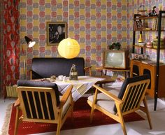 70 Years of Ikea, as told by showroom apartments. This space has a red area rug, wood coffee table, hanging globe lamp, open shelving, patterned walls, colorful curtains and a retro TV.