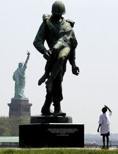 With the Statue of Liberty in the distance, Jaden Crandell, 10, salutes a statue by Natan Rapoport depicting a soldier carrying a World War II concentration camp survivor during a Memorial Day outing with his family, on May 28, 2012, at Liberty State Park in Jersey City, N.J.