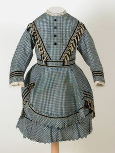 circa 1872 girl's dress, blue and white checked silk dress in two pieces trimmed with white edged black velvet ribbon, black and white fringing and machine lace with black velvet buttons.