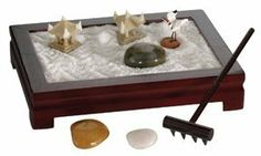 """Toysmith Mini Zen Garden by Toysmith. $9.14. Tiny Japanese Rock Garden. Sand represents ocean. Rocks represents islands. Perfect for small spaces and desktops.. This tiny Japanese Rock Garden is perfect for small spaces and desktops. 3"""" x 4"""". Includes rocks (representing islands), sand (representing ocean) and a rake for making the garden your own creation."""