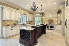 Massive luxury white kitchen with extra long central island which includes wine rack. Island in dark wood while kitchen cabinets in white.