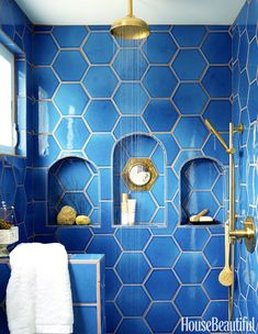 Blue hex wall tiles in shower with gold grout